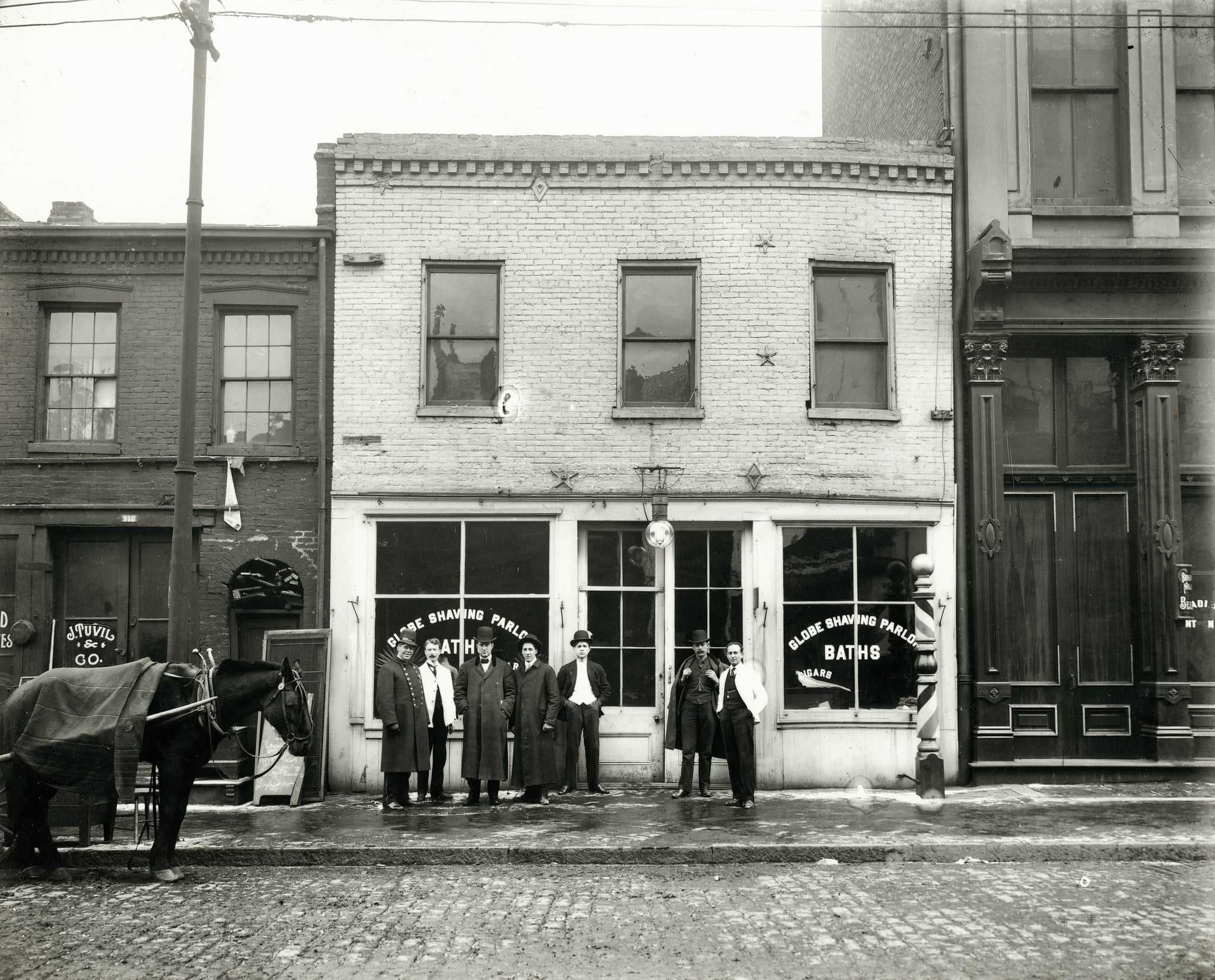 Group of men standing in front of the Globe Shaving Parlor at 1015 Carr. Photograph, ca. 1910. In the surrounding blocks lived Italians, Yiddish-speaking Russians and Hungarians, and African American families from the South.