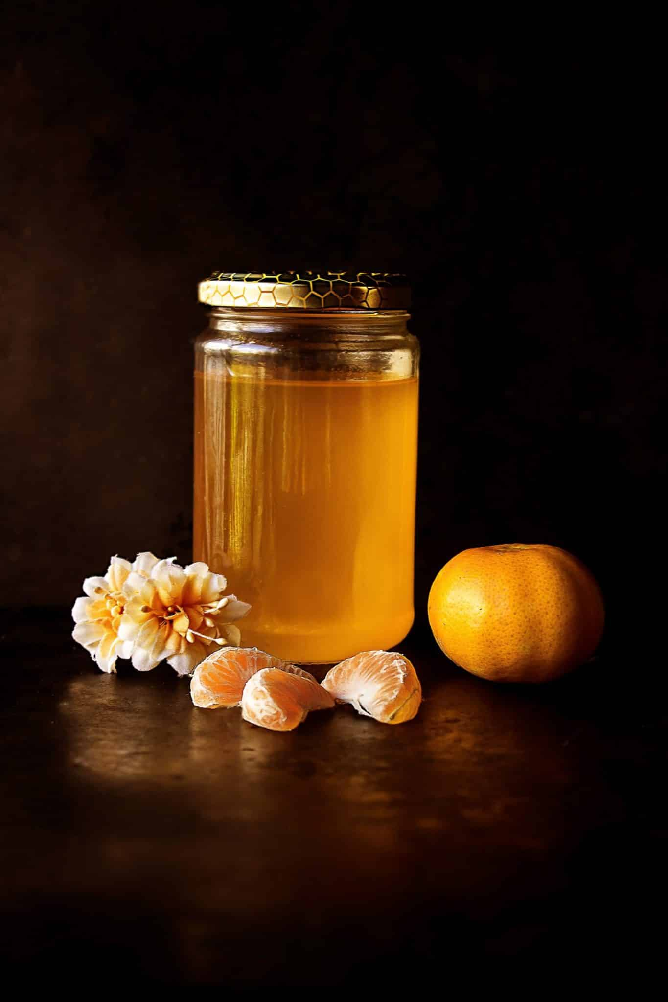 Honey in a jar, clementine, and a flower