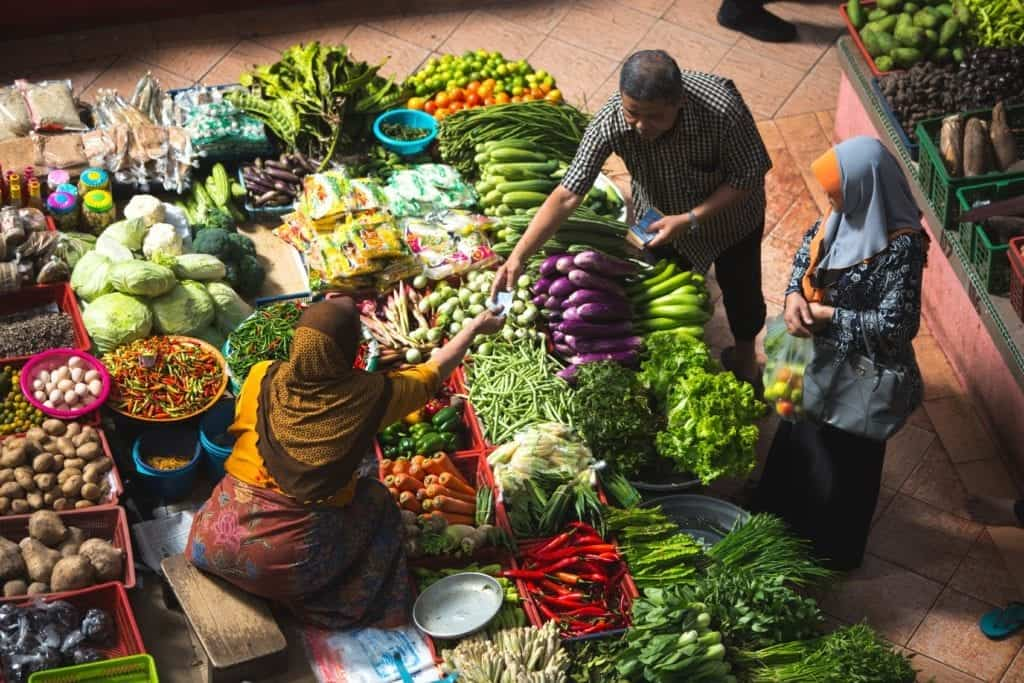 People at a market buying vegetables